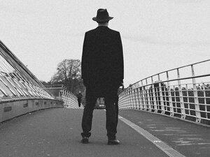 A man in a long dark coat.